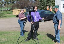 NNY dairy farmer John E. Peck talks with reporter Elaine Avallone of the Carthage Republican-Tribune and Patrick Malowski of WWNY TV 7.